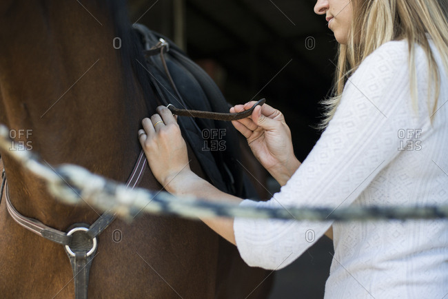 Young woman applying saddle at horse\'s back