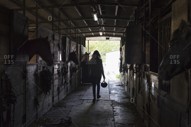 Young woman walking in horse stable