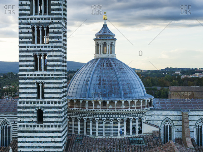 Siena, Italy - May 9, 2017: Striped facade of a tower and dome roof of Siena Cathedral
