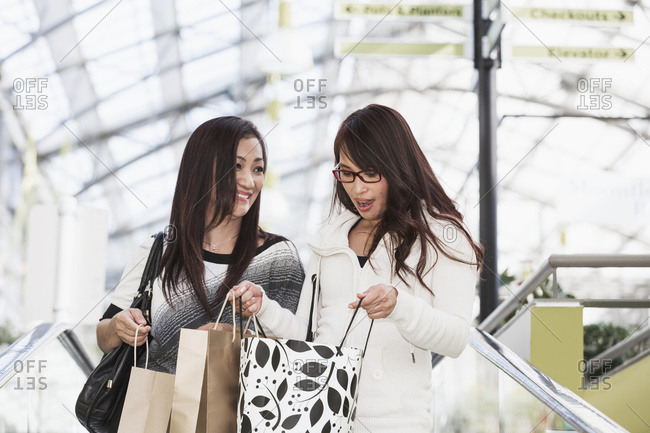 Two girlfriends out shopping together at a shopping mall, St. Albert, Alberta, Canada