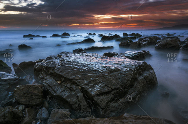 Water surrounds the rocks on the beach and the clouds glow orange and pink at sunset over the horizon, Tarifa, Cadiz, Andalusia, Spain