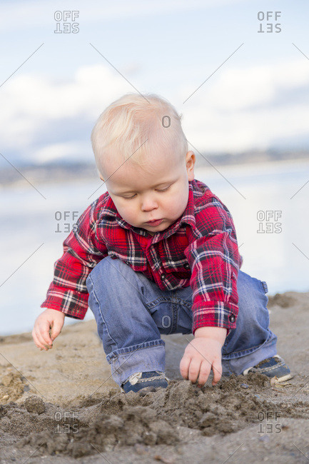 A young boy in a red plaid shirt and jeans plays in the sand by the ocean, Surrey, British Columbia, Canada