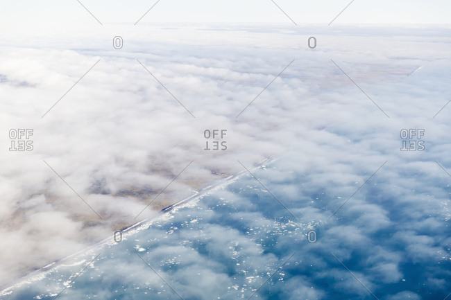 Aerial view of the North Slope coastline shrouded in a thin layer of clouds, icebergs floating in the Arctic Ocean, Deadhorse, Alaska, United States of America