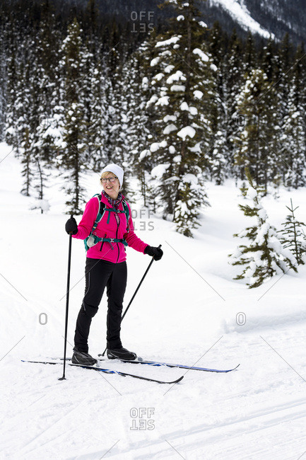 Female cross country skier smiling along groomed trail with snow covered trees in background, Lake Louise, Alberta, Canada