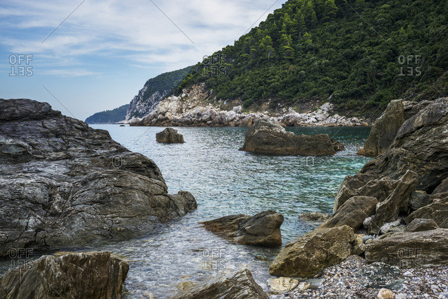 View of the coastline of a greek island with rocks and a forest on the mountainside, Sporades, Thessalia Sterea Ellada, Greece