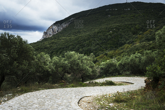 A winding cobblestone path over a forested landscape of hillsides and cliffs on a greek island, Skiathos, Greece