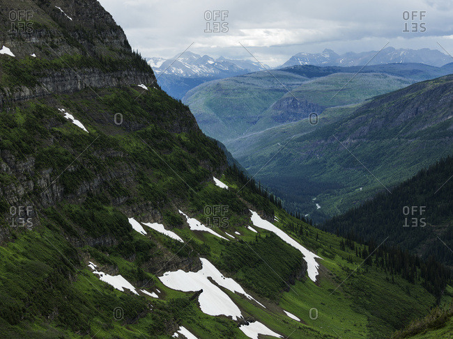 Extreme terrain in mountain range under cloudy sky, Glacier National Park, Montana, United States of America
