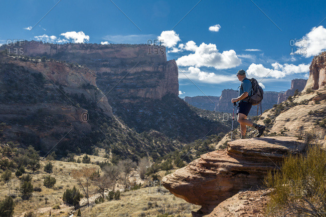 A male hiker enjoys a sunny view of the Colorado National Monument, Colorado, United States of America