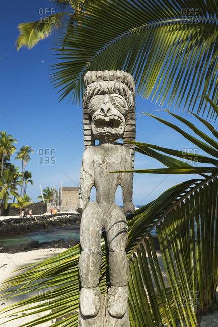 Tiki carving in Pu'u Honua O Honaunau National Park in Hawaii with heiau in background, Honaunau, Island of Hawaii, Hawaii, United States of America