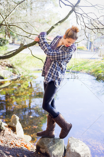 A young teenage girl casually entertains herself along the waters edge while holding a tree branch, New Westminster, British Columbia, Canada