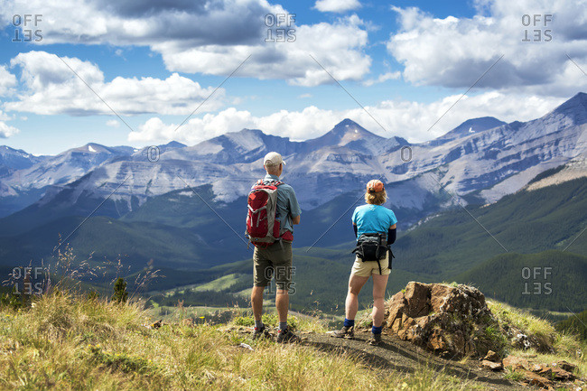 Male and female hikers standing on top of rocky hill overlooking mountain range and valley with blue sky and clouds, West of Bragg Creek, Alberta, Canada