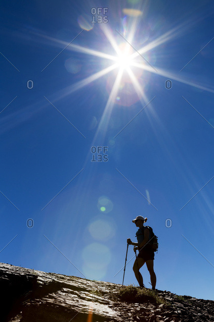 Silhouette of female hiker on rocky ridge with blue sky and sunburst, Waterton, Alberta, Canada