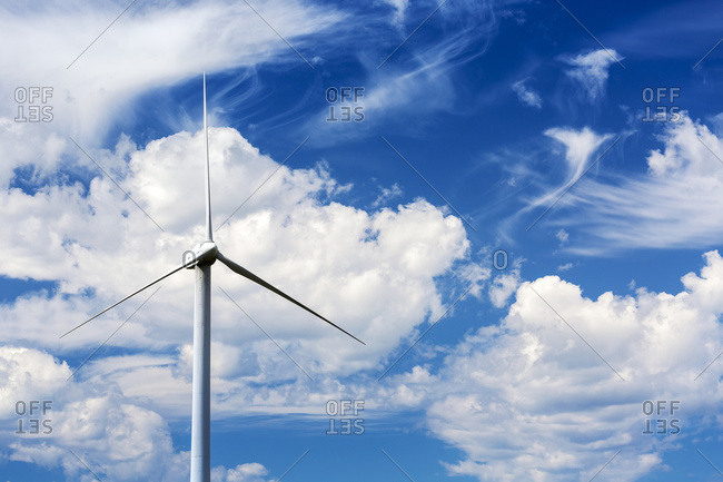 Close up of a large wind mill\'s blades with clouds and blue sky, North of Glenwood, Alberta, Canada