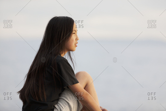An Asian teenage girl sits looking out over the water, British Columbia, Canada