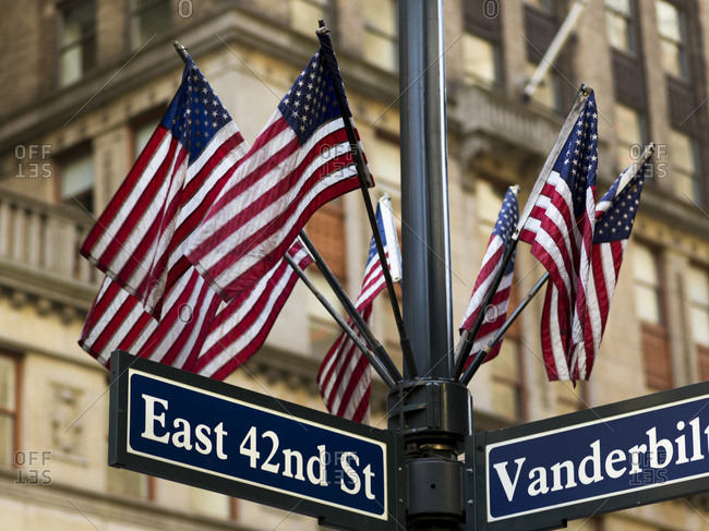 Flag pole stock photos offset american flags on a pole above the street signs at the intersection of east 42nd street sciox Image collections