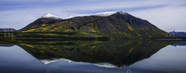 Reflection of the mountains surrounding Carcross reflected in the still waters, Yukon, Canada