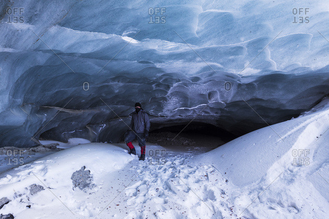 "A man poses in front of a cave at the terminus of Fels Glacier (commonly misspelled ""Eel"" Glacier) in the Alaska Range in winter, Alaska, United States of America"