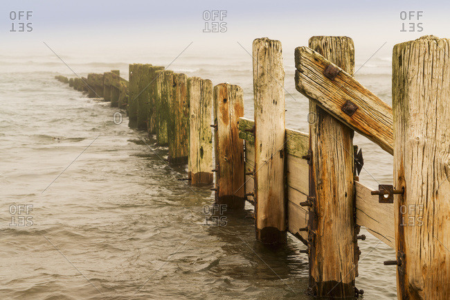 A wooden fence leading out in the ocean water, Berwick, Northumberland, England