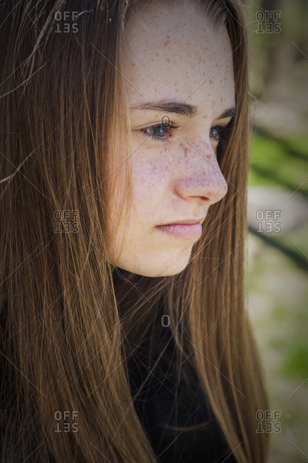 Portrait of a teenage girl with freckles staring ahead with a solemn look, Connecticut, United States of America