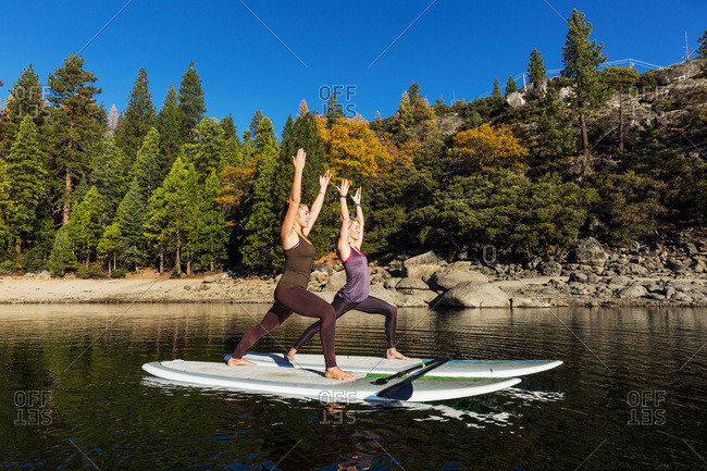 Fitness models doing yoga on a paddleboard on Pine crest Lake, California, United States of America