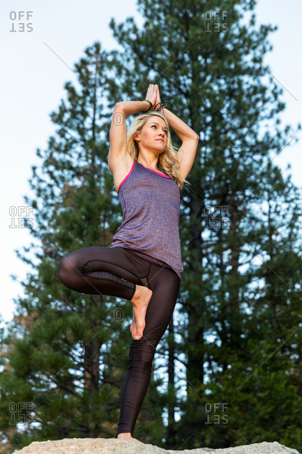 Young woman doing yoga on top of a boulder, California, United States of America