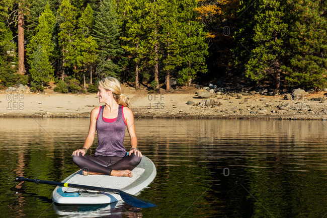 Young woman sitting on a paddle board ready for yoga on Pine crest Lake, California, United States of America