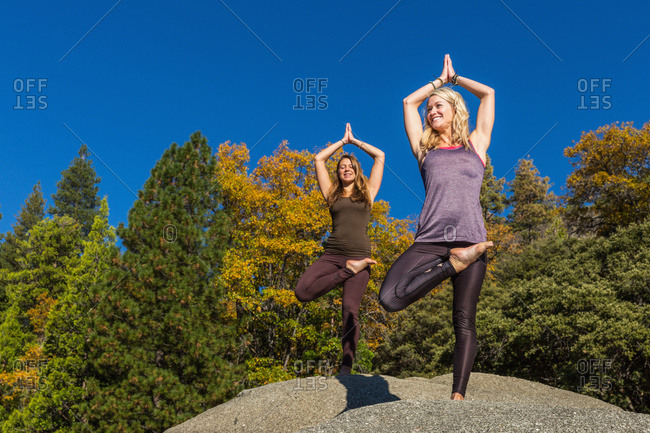 Fitness models doing yoga on a boulder, Pine crest Lake, California, United States of America