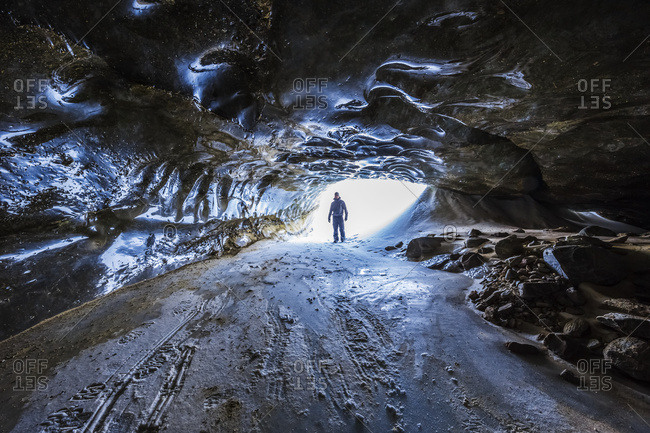 A man stands in the entrance to a lengthy tunnel beneath the ice of Castner Glacier in the Alaska Range, Alaska, United States of America