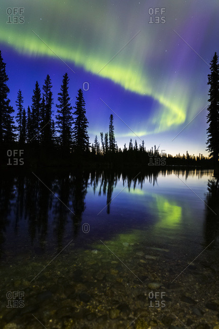 The aurora borealis reflects in the Clearwater River in Delta Junction shortly before sunrise, Alaska, United States of America