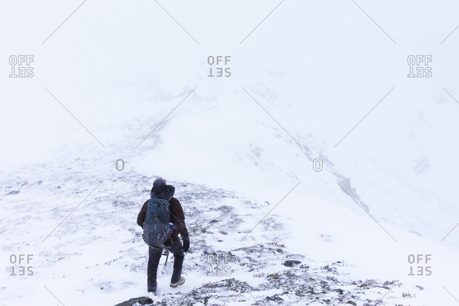 A hiker descends a ridge in blowing snow after climbing high above Trims Creek in a portion of the Alaska Range known as the 'Delta Mountains' in early winter, Alaska, United States of America