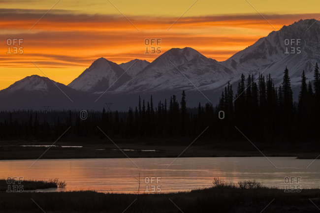 Sunrise over the pond and mountains along the Parks Highway in autumn, near Cantwell in interior Alaska, Alaska, United States of America