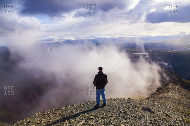 A man watches clouds swirling beside a ridge high in the Alaska Range, Alaska, United States of America