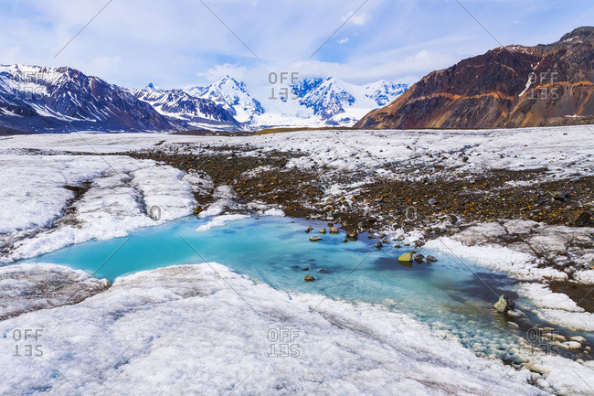 A turquoise pool of water lies on the surface of Gakona Glacier in the Alaska Range, Alaska, United States of America