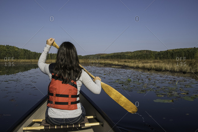 Woman canoeing in Algonquin Park, Ontario, Canada
