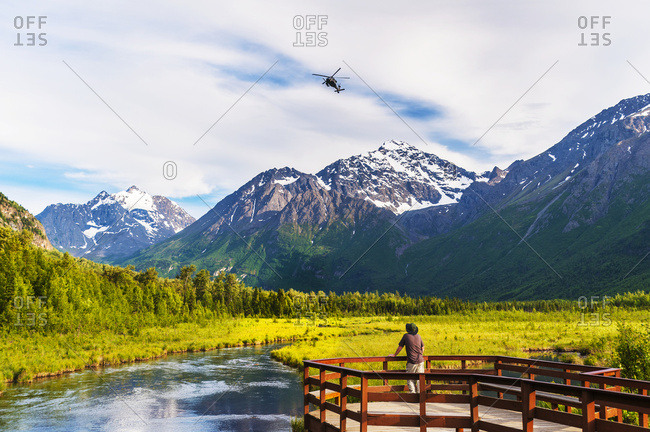 A man is standing on the Eagle River Nature Center boardwalk while a Black Hawk helicopter flies over head in the Chugach State Park in South-central Alaska, USA