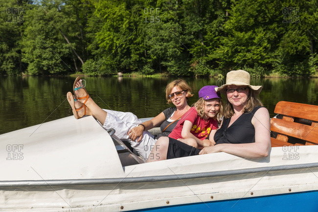 Two women and a girl on a paddle boat on a calm river surrounded by dense forests on a sunny day, Steinbrucker Teig, Hessen, Germany