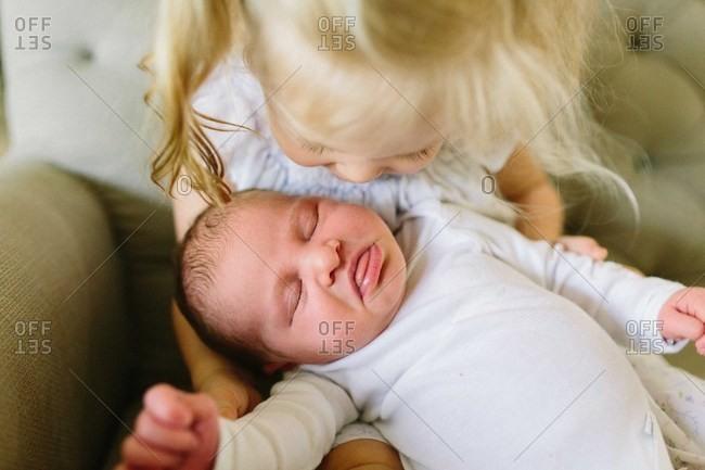Toddler girl holding sleepy baby sister