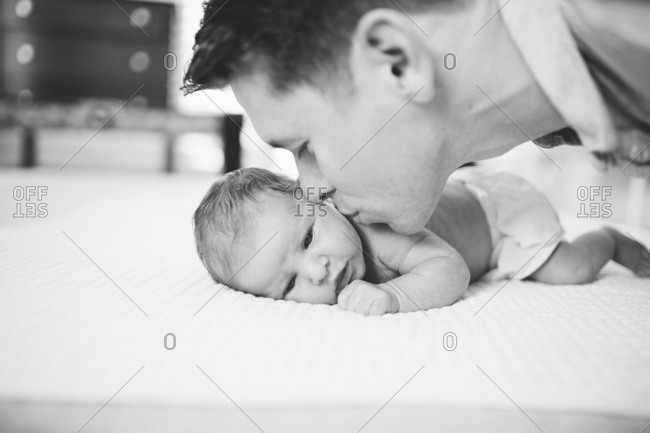 Father kissing newborn baby's cheek in black and white