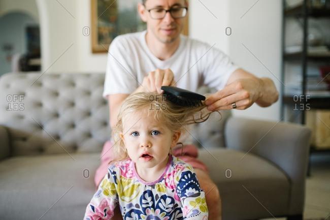 Man brushing little girl's hair