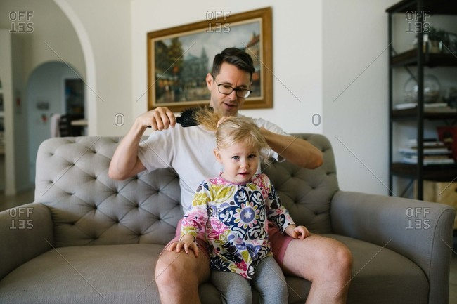 Man styling little girl's hair