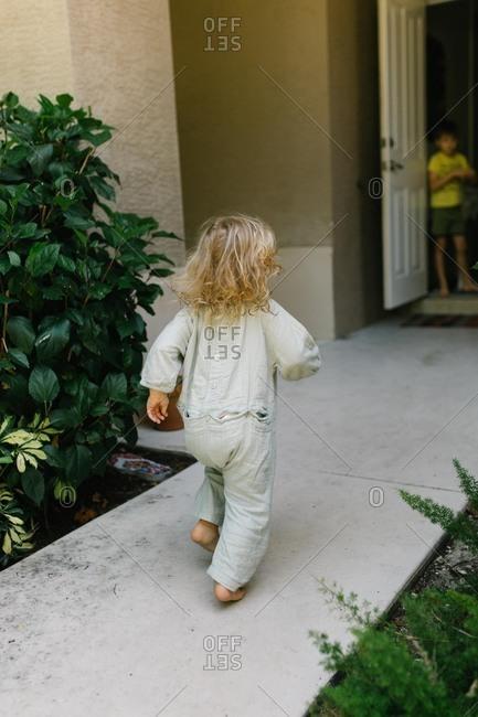 Little girl running on sidewalk from behind