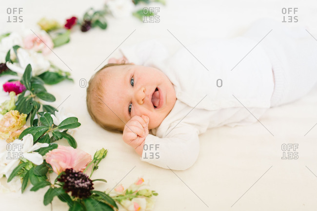 Happy baby lying on a white blanket with flowers