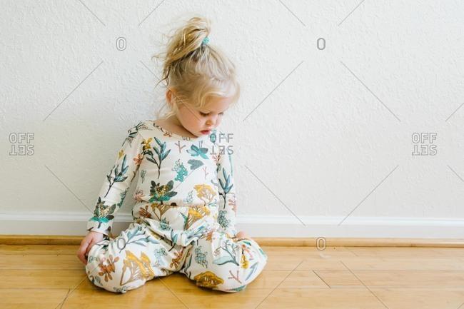 Little girl sitting on hardwood floor looking down