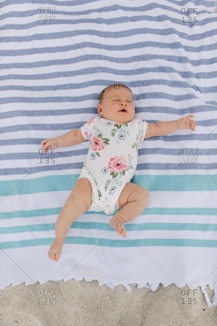 Infant lying on a blanket on a beach