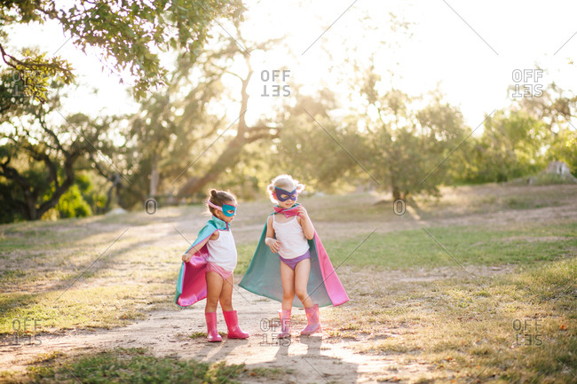 Two preschool-aged girls in superhero capes and masks