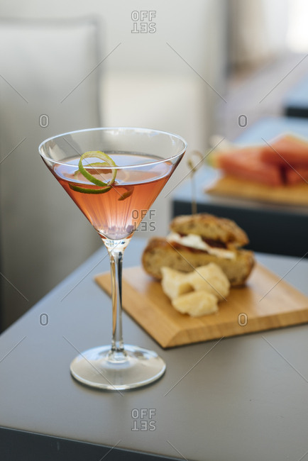 Pink cocktail with lime rind garnish served with sandwich