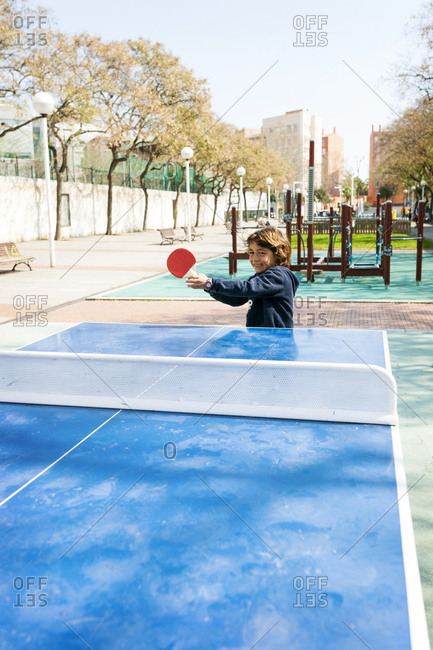 Boy playing table tennis outside