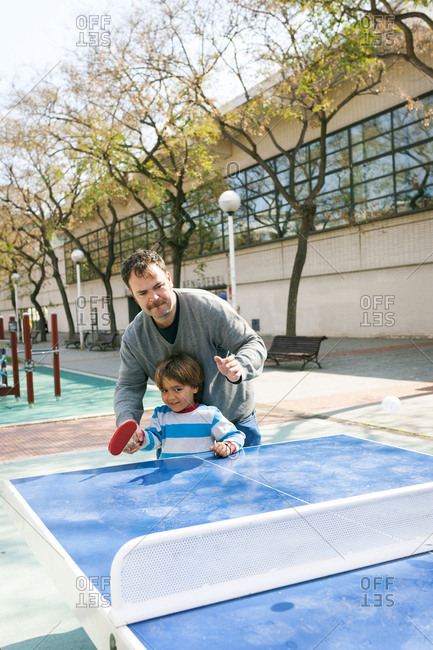 Father helping his son playing table tennis