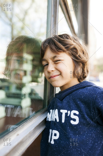Cute young boy winking and leaning against window