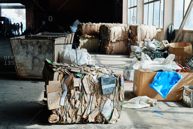 Blocks of compressed cardboard ready for reuse lying at waste recycling plant